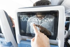 Traveller pressing Go shop now on touchscreen monitor inside the aircraft. Traveller pressing Go shop now on touchscreen monitor ine the aircraft stock photography