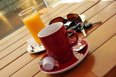 Traveller'S Coffee Break. Red cup of coffee, juice, sunglasses and car key on table on gas station Stock Images