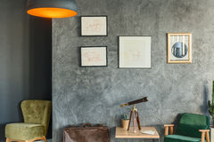 Traveller`s living room. Design decorated with drawings and green chairs stock images