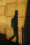 Traveller's Shadow. The shadow of a passing traveller cast by the evening sun onto a wall Royalty Free Stock Photo