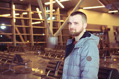 Traveller smiling in an airport lounge. On the background of the seats at the airport a young man with a beard. Concept travel Stock Image