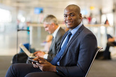 Traveller tablet pc. Handsome african business traveller using tablet pc at airport Stock Photos