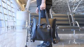 Traveller Takes His Bag for Flight from Waiting Chair at Airport. 4k , high quality Royalty Free Stock Photography