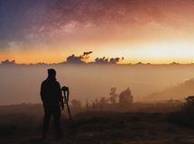 Traveller taking photograph of landscape sunrise and sky full of stars in dawn. Traveller taking photograph of landscaped sunrise and sky full of stars in dawn stock images
