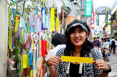 Traveller thai woman join and writing her wishes small pieces of. Paper and hanging them on bamboo in Tanabata or Star festival Japanese festival on July 7 Royalty Free Stock Images