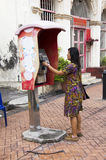 Traveller thai woman using public telephone or payphone booth ca Stock Images