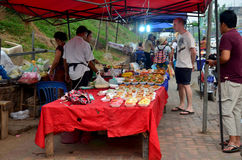 Traveller travel and buy food from Laotian people at local night Royalty Free Stock Photo