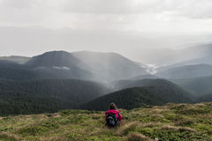 Young female hiker with backpack sits in grass on top of hill. Traveller on trip to mountains taking rest at mountain peak and looking at heavy thunder rain Stock Images