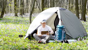 Traveller uses a tablet outdoors. Backpacker uses a tablet outdoors stock video