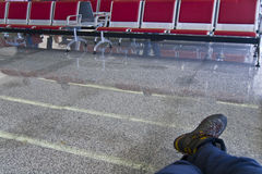 Traveller in waiting area. Crossed feet of traveller in deserted waiting area Stock Photo