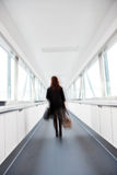 Traveller walking. Motion Blured woman in the corridor of an airport Royalty Free Stock Image