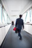 Traveller walking. Motion Blured business people in the corridor of an airport Royalty Free Stock Photos