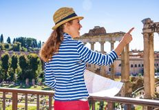 Traveller woman against Roman Forum holding map and pointing Stock Photography