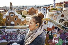 Traveller woman in Barcelona listening audioguide. Barcelona signature style. modern traveller woman in coat at Guell Park in Barcelona, Spain listening Royalty Free Stock Photos