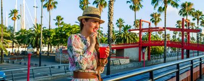 Traveller woman on embankment in Barcelona drinking red beverage Royalty Free Stock Images