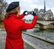 Traveller woman on embankment in Paris taking photo with phone Stock Photography