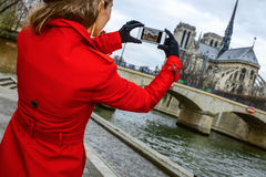 Traveller woman on embankment in Paris taking photo with phone Royalty Free Stock Images