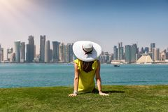 Traveller woman enjoys the view to the skyline of Doha, Qatar. From a park stock images