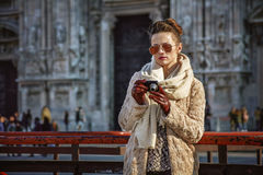 Traveller woman in front of Cathedral viewing photos on camera. Rediscovering things everybody love in Milan. trendy traveller woman in fur coat and sunglasses Stock Images