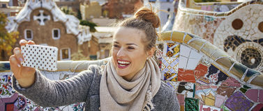 Traveller woman at Guell Park taking selfie with mobile phone. Barcelona signature style. smiling trendy traveller woman in coat at Guell Park in Barcelona stock image