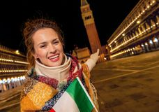 Traveller woman with Italian flag pointing at St Mark`s Campanil Royalty Free Stock Image