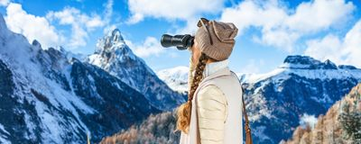 Traveller woman looking into the distance through binoculars Stock Images