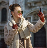 Traveller woman in Milan with digital camera taking selfie Stock Photography