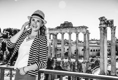 Traveller woman near Roman Forum speaking on cell phone. Roman Holiday. smiling stylish traveller woman near Roman Forum in Rome, Italy speaking on a cell phone Stock Image