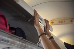Traveller woman open overhead locker on airplane Royalty Free Stock Photography