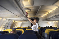 Traveller woman open overhead locker on airplane Stock Photos