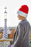 Traveller woman in Santa hat at Guell Park looking into distance Stock Photo