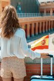 Traveller woman with trolley bag, Spain flag and green smoothie. Seen from behind elegant traveller woman with trolley bag, Spain flag and green smoothie near stock photography