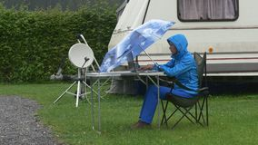 A traveller works on laptop under blue umbrella under rain near caravan. A tourist in waterproof clothing works at the computer under umbrella under rain in stock video