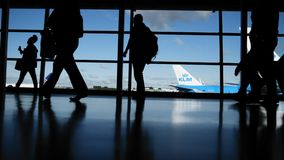 Travellers in airport in front of window, silhouette. Blue colors stock footage