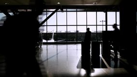 Travellers in airport terminal. In silhouette stock footage