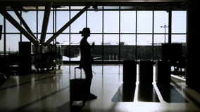 Travellers in airport terminal. In silhouette stock video footage