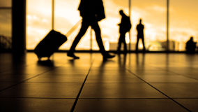 Travellers in airport walking to departures by escalator in front of window, silhouette, warm Stock Photo