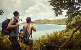 Travellers with backpacks watching through binoculars enjoying v Stock Photo