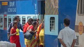 Travellers boarding an Indian train. Madurai, India - March 10, 2018: Passengers embarking on an express train about to depart for Chennai in Tamil Nadiu state Stock Images