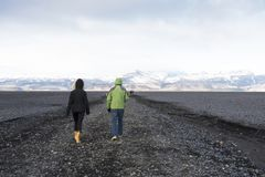 People walk on black sand beach in south Iceland. Travellers couple walk on black sand beach in south Iceland Stock Image