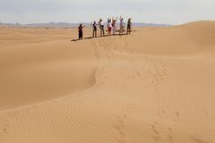 Travellers on the dune. Of Erg Chigaga, Morocco. Erg Chigaga is one of Morocco's two Saharan ergs, large dunes formed by wind-blown sand Stock Photography