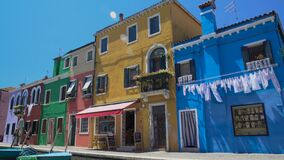 Travellers enjoying leisure trip, taking photo in colorful Burano island street. Stock footage stock video footage