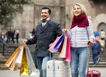 Travellers enjoying shopping tour. Happy mature couple of travellers enjoying shopping tour during weekend Royalty Free Stock Photography