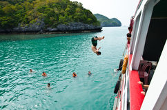 Travellers leap from the deck into the sea. Stock Photography