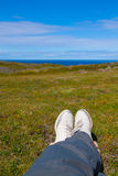 Travellers legs, first-person view. Male traveler sitting in summer mountains at sunset, point of view shot Royalty Free Stock Photography