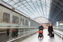 Travellers in London Railway Station. LONDON, UK - JANUARY 28, 2016: Two women walk under arched roof of kings Cross St Pancras railway station Royalty Free Stock Photos