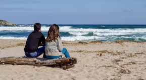 Travelers looking to the horizon. Man and women sitting on the beach looking to the sea, autumn scene Stock Images