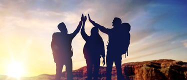 Travellers making high five over sunrise royalty free stock photo