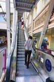 Travellers pass through a BTS Skytrain station. BANGKOK, THAILAND - JAN 4, 2015: Unidentified rail travellers pass through a BTS Skytrain station during rush Stock Photos
