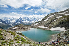 Travellers rest on brink of mountain lake, Chamonix Royalty Free Stock Photos
